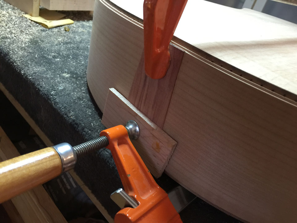 """CLAMPS HOLD IT IN PLACE AS THE GLUE DRIES, THEN THE BINDING ROUTING IS CONTINUED OVER THE """"FLASH""""."""
