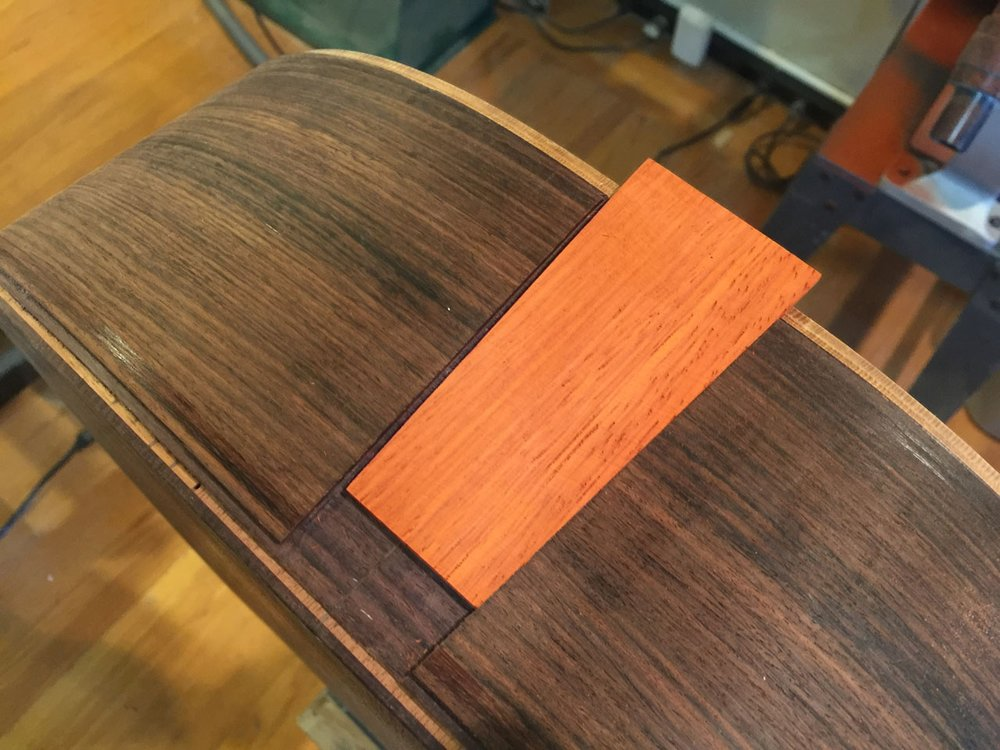 THE WOODEN PIECE IS CLOSELY-FITTED AND GLUED INTO PLACE OVER THE BOTTOM BODY SEAM.