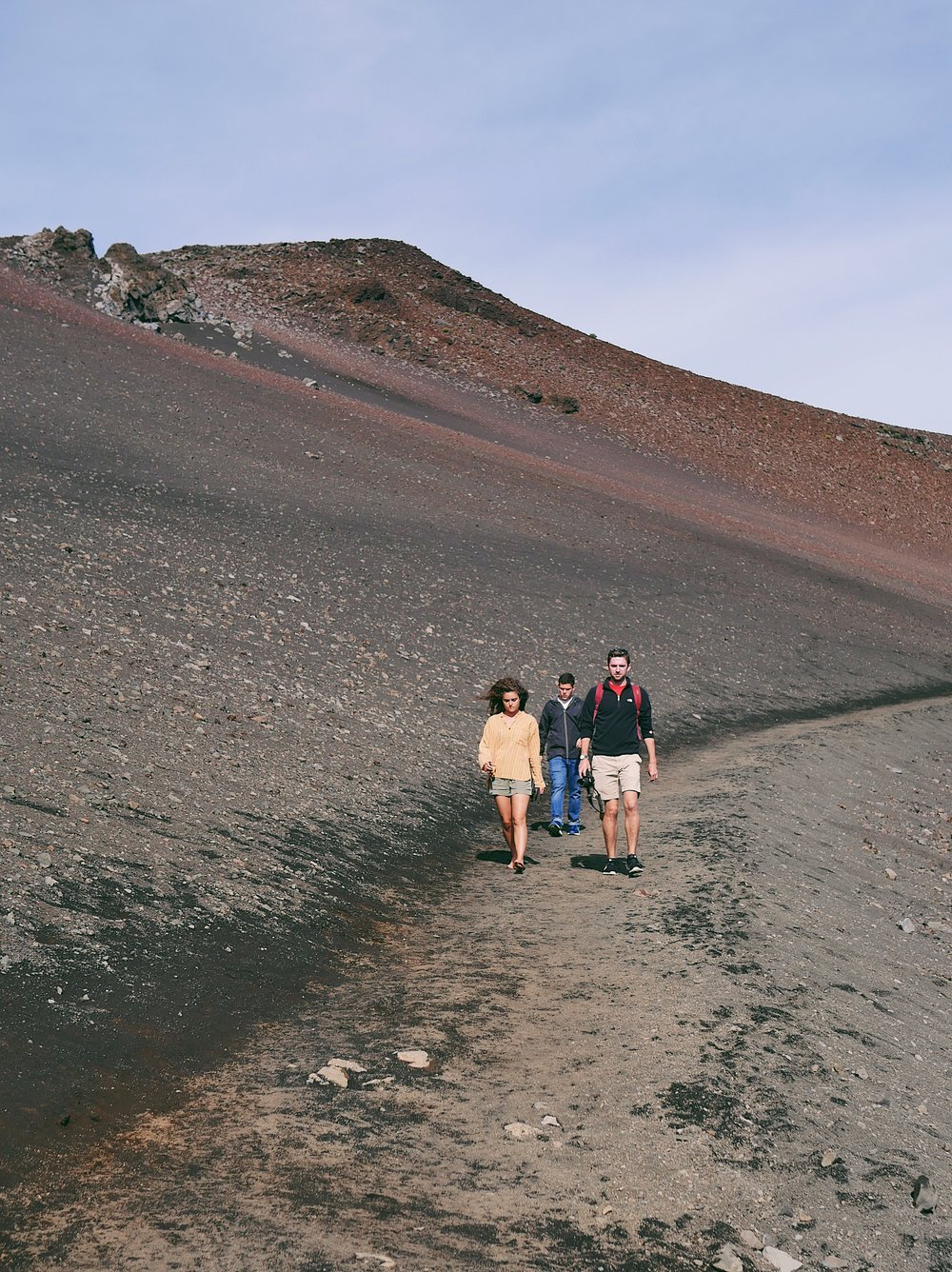 Emily Lutz, Zach Delgado, and Tyler Brewer walk along a path at the summit of Haleakalā