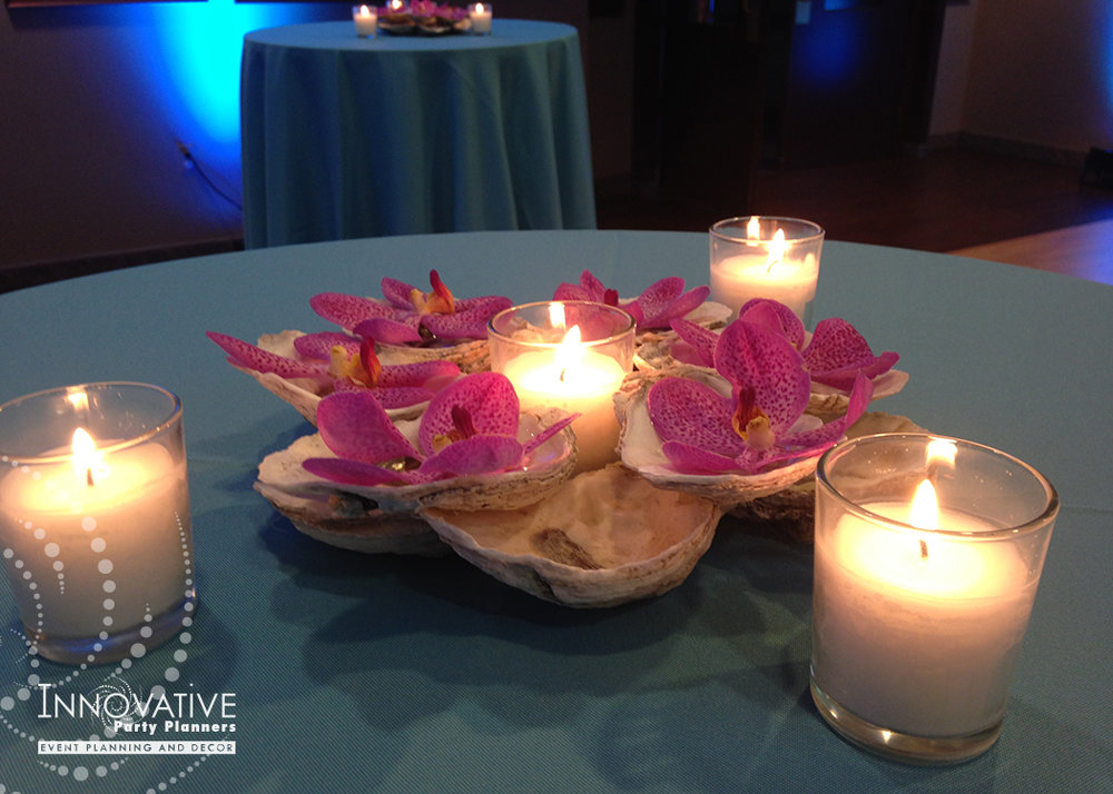 Cocktail tables featured pink orchids floating on our hand made oyster shell votives.