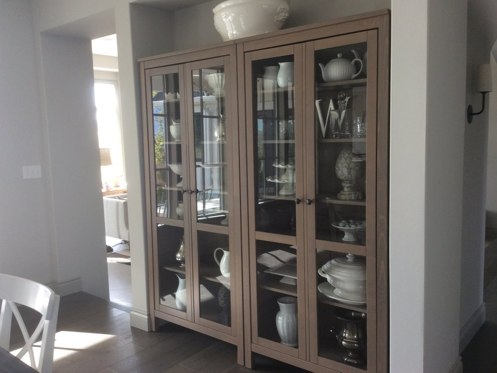 The dining room china cabinet displaying white enamelware.