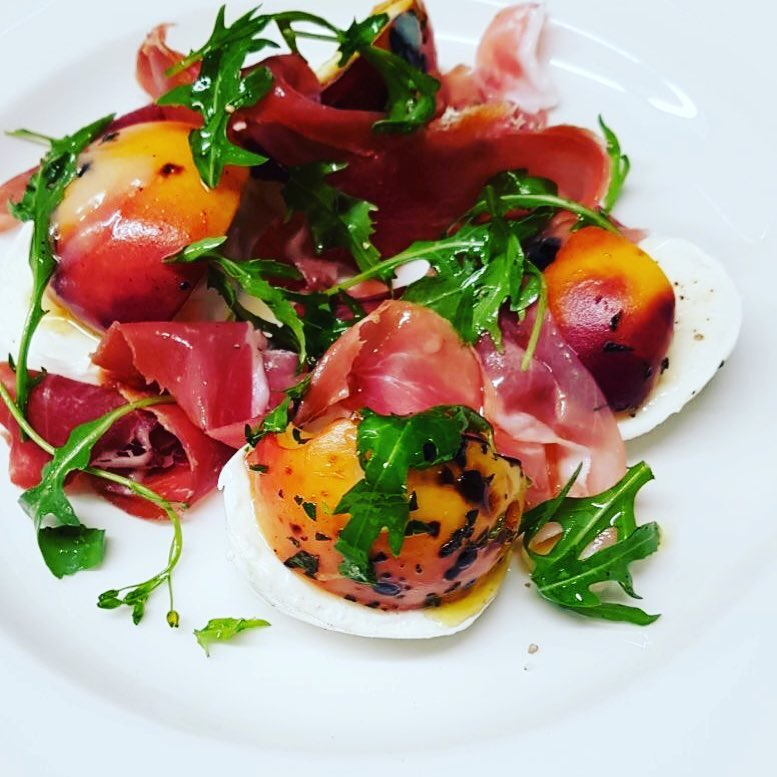 Grilled peaches, prosciutto, That's Amore Cheese mozzarella and roquette