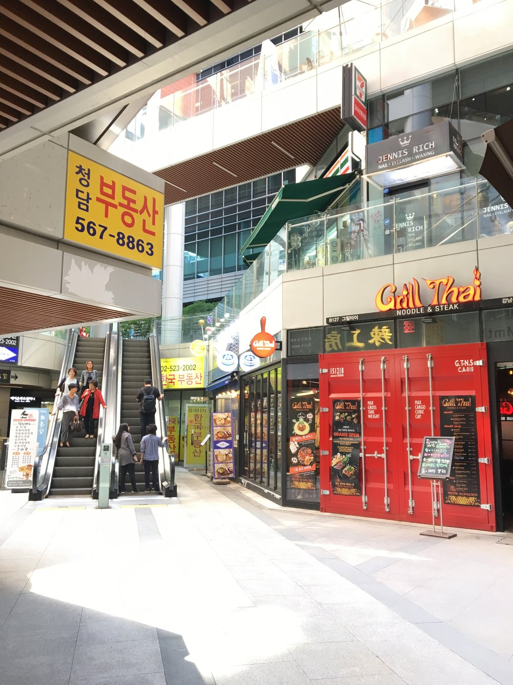 6.當您看到手扶梯時,向右走會看到一家Grill Thai的餐廳 - 電梯入口就在餐廳右邊.