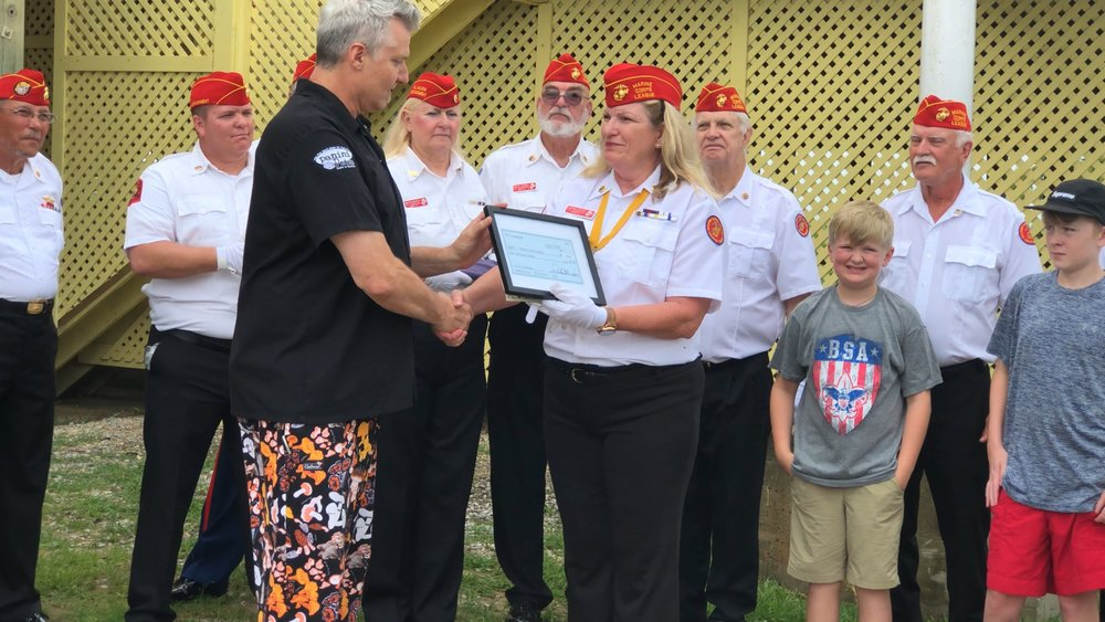 2018 PR Foundation co founder Pete Blohme presenting a check to the to the local Marine Corp league for a electric wheelchair for a war veteran from Alabama.