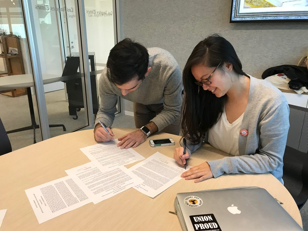 L.A. Times Guild co-chair Anthony Pesce and vice chair Kristina Bui sign the tentative agreements on December 20, 2018.