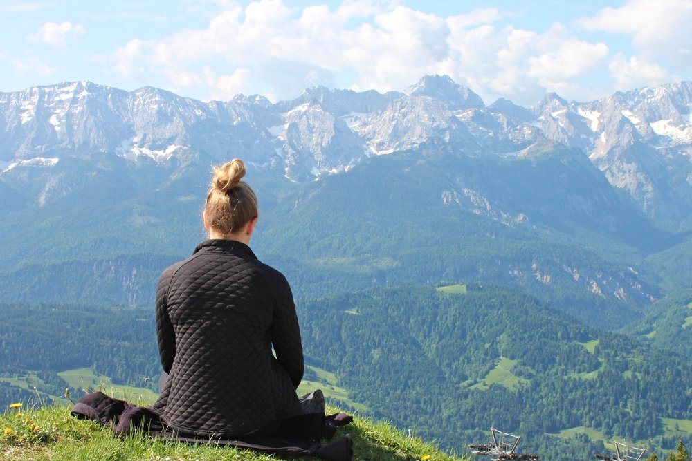 Picture for Guideful blog post - Woman meditating on a mountain
