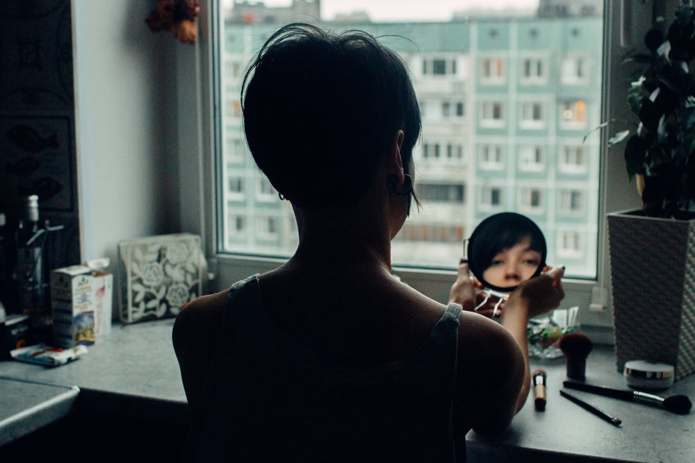 Woman with anxiety looking at mirror