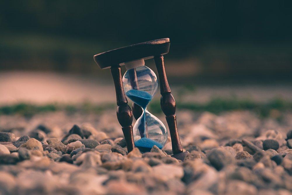 blue sand passing through hour glass