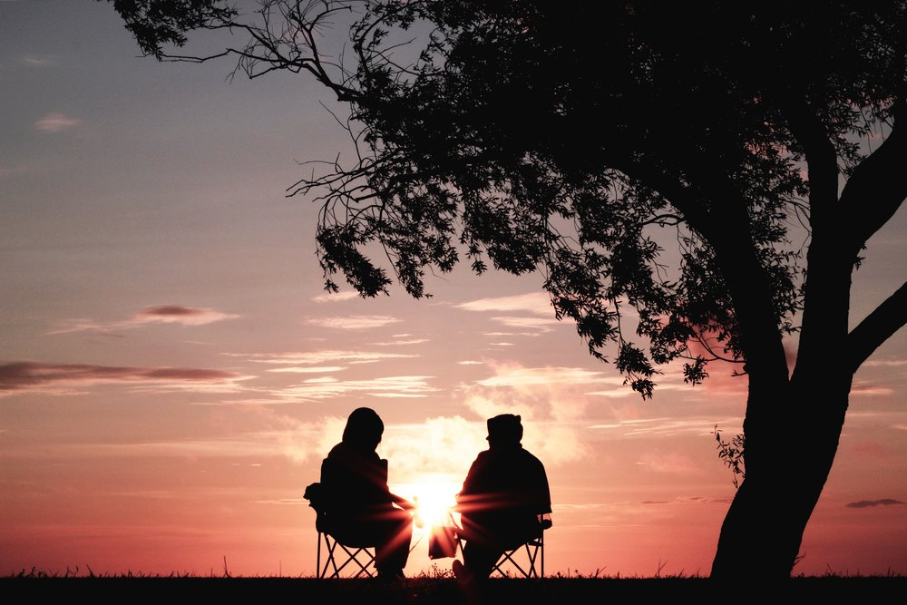 two men sitting in camp chairs watching sunrise