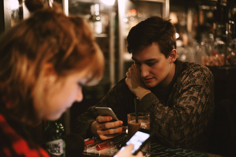 two milennials sitting at a table staring at their phones
