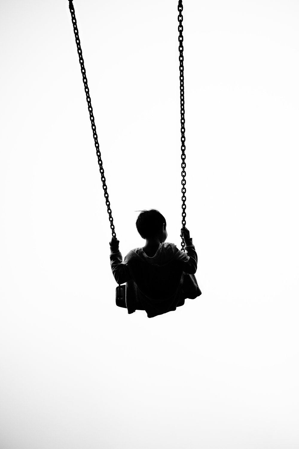 black-and-white photo of child on swing