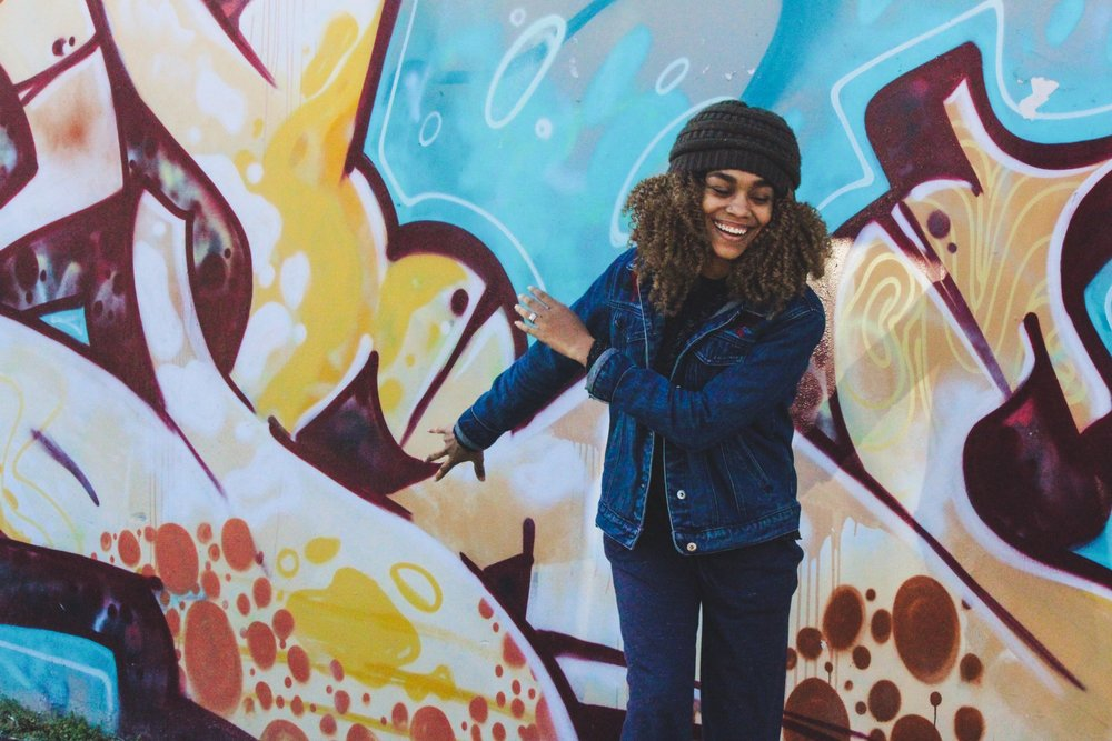 African American woman smiling and dancing in front of a large graffiti mural