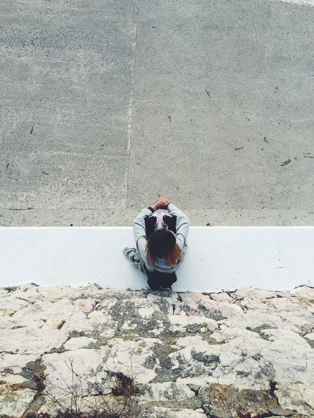 aerial shot of an anxious woman sitting on a ledge