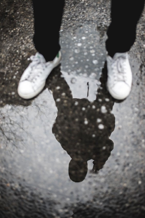 anxious man looking at reflection in puddle
