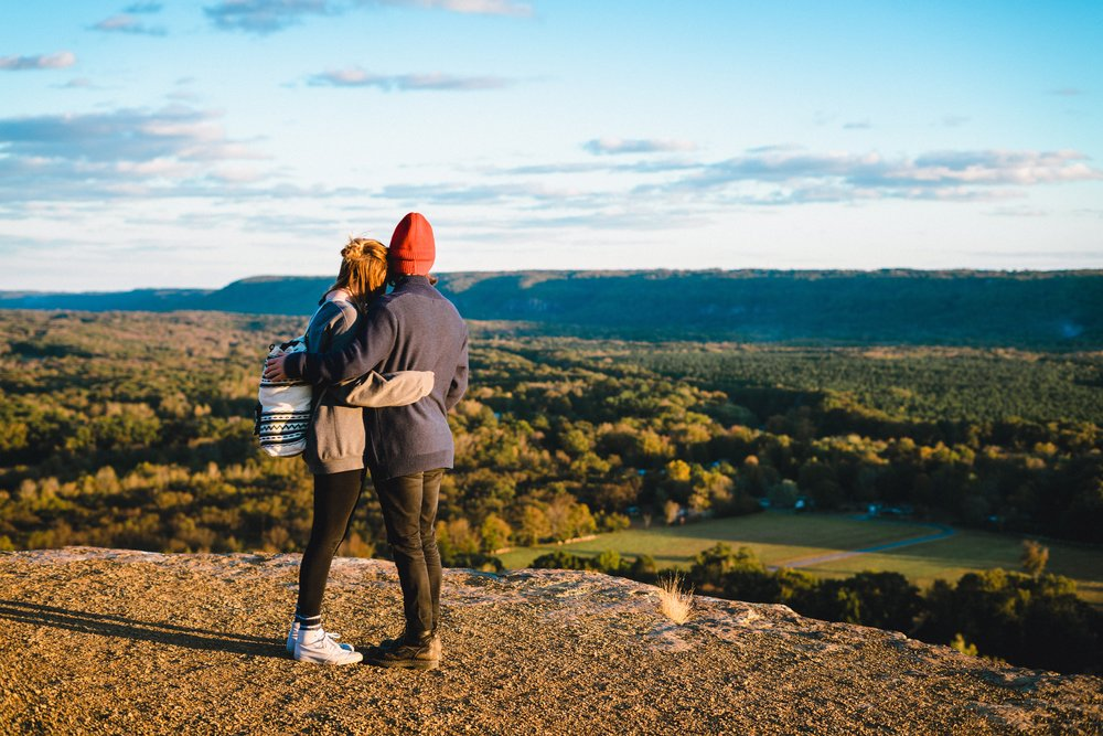 man and woman hugging while looking at beautiful landscape