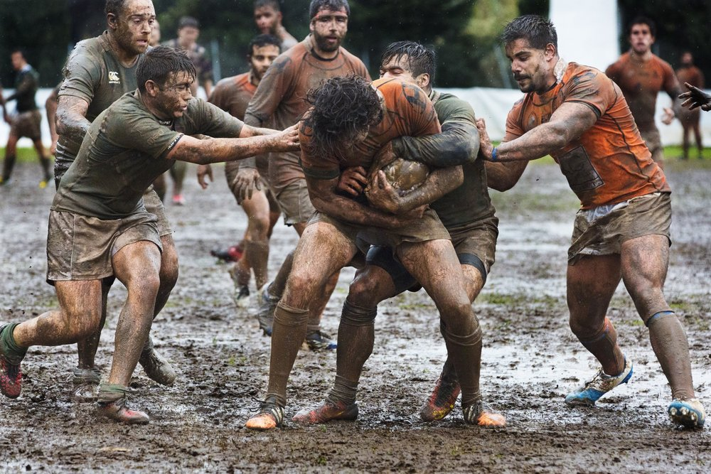 strong men playing rugby in muddy field