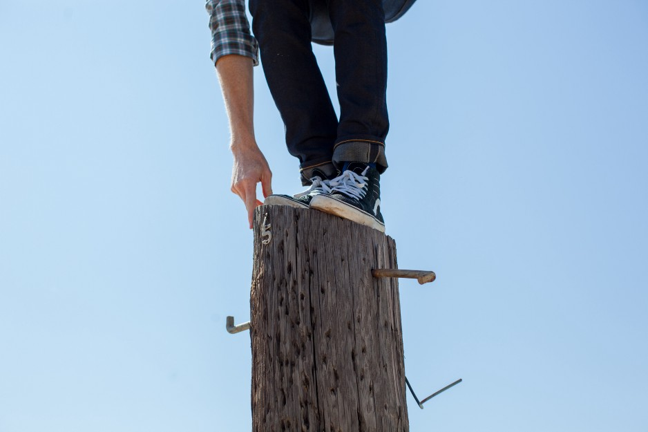 man balancing himself on top of telephone pole