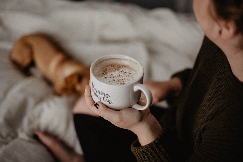 woman caring for mental health by sitting on couch with coffee cup and dog