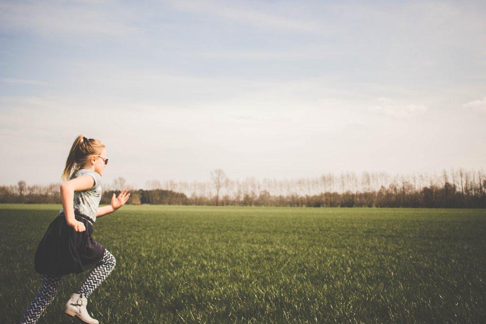 adolescent girl running across grass field