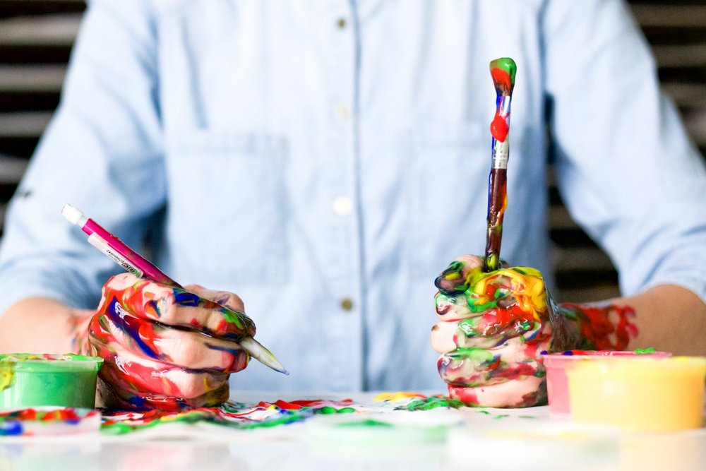 man wearing dress shirt with paint on his hands holding a paintbrush and a pencil