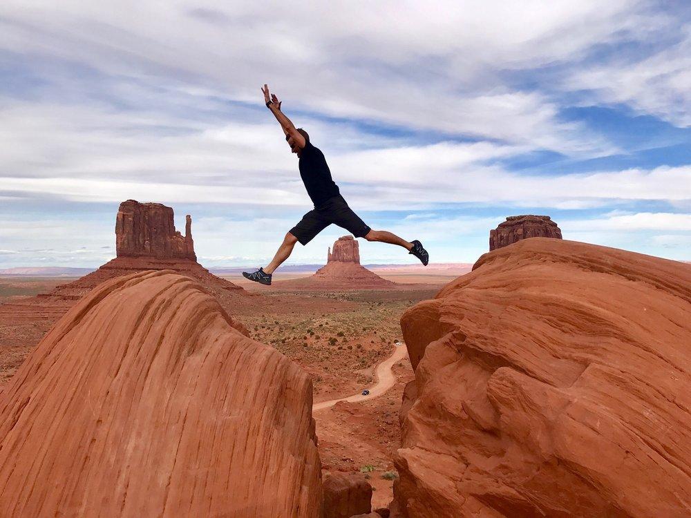 man in midair jump between red sandstone formations