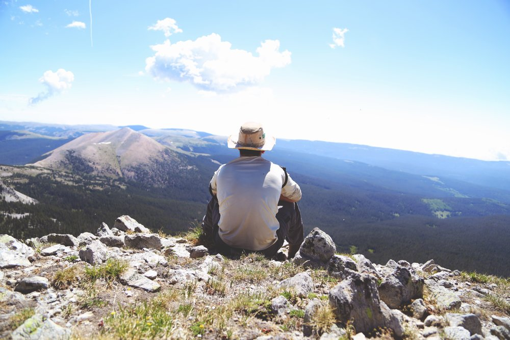 man sitting on mountain summit looking at landscape