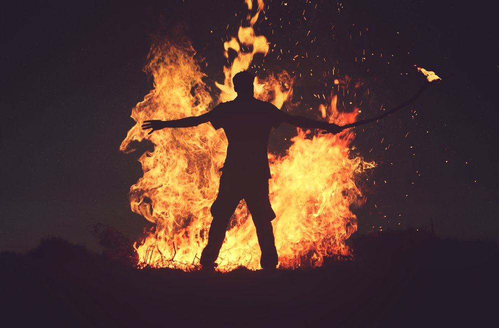 man conquering post-traumatic stress standing in front of bonfire