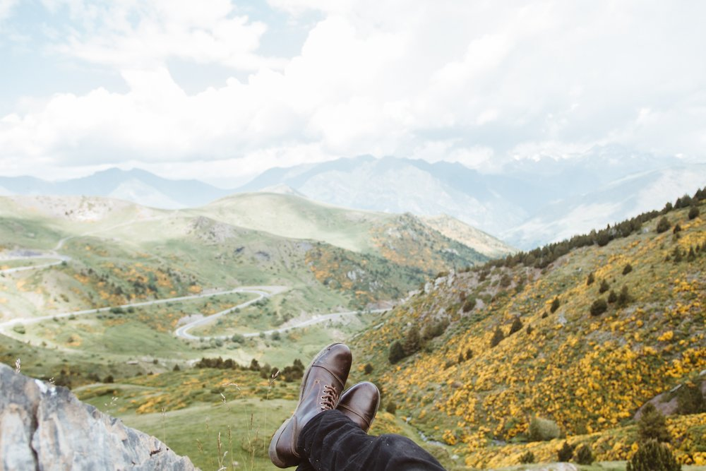 image of man's boots resting while overlooking a mountain range