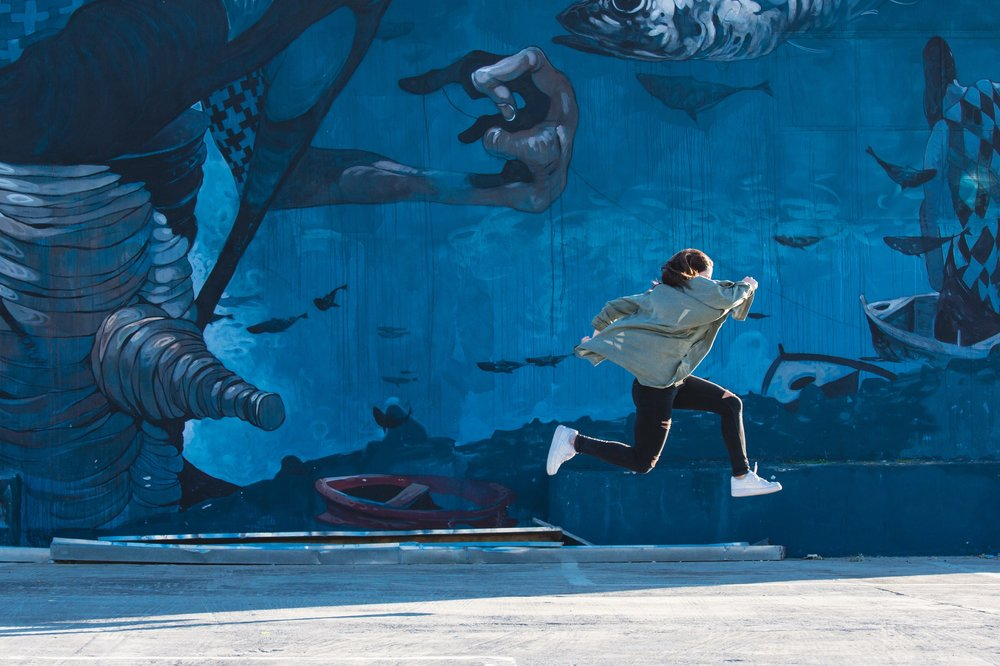 woman with white sneakers running through air in front of blue mural