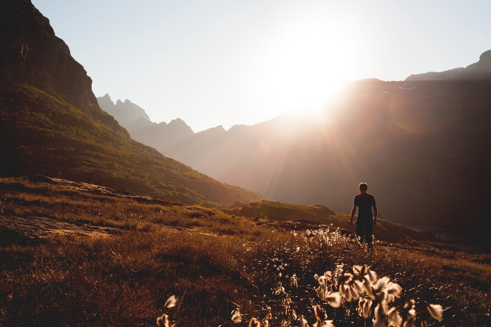man walking in field with sun shining over mountains