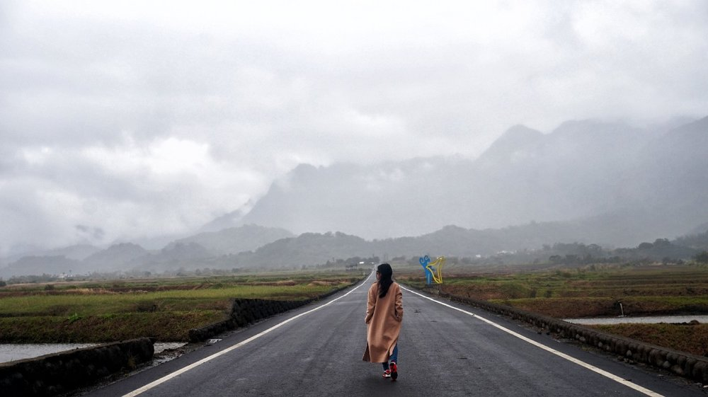 woman with long coat walking down middle of road towards mountains