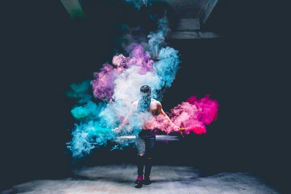 shirtless man wearing bandanna spraying colored smoke