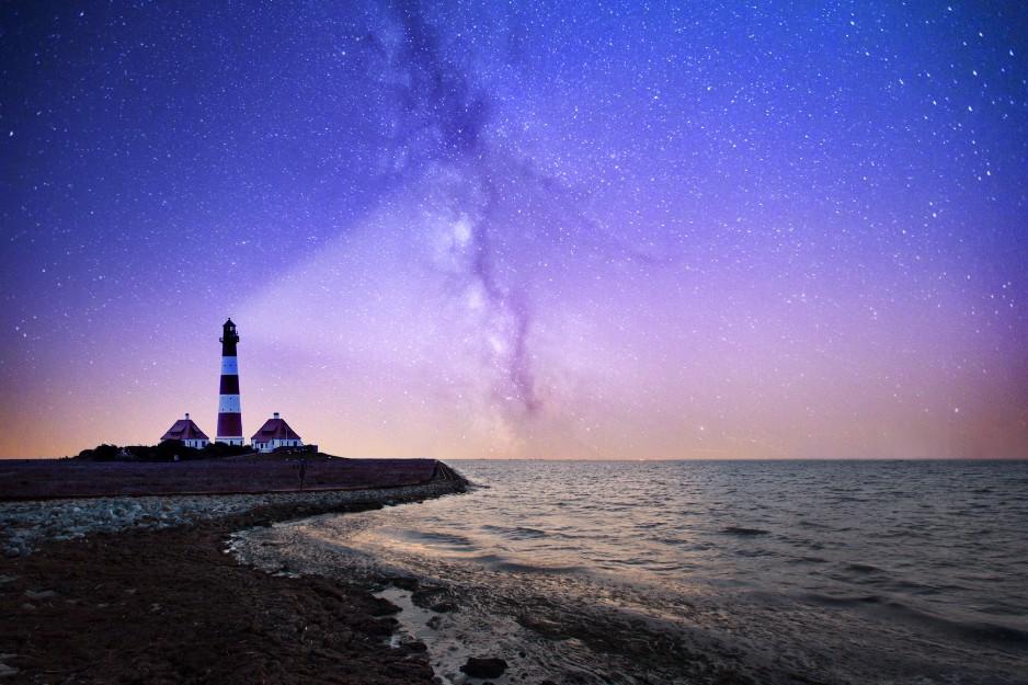 lighthouse lighting up starry sky