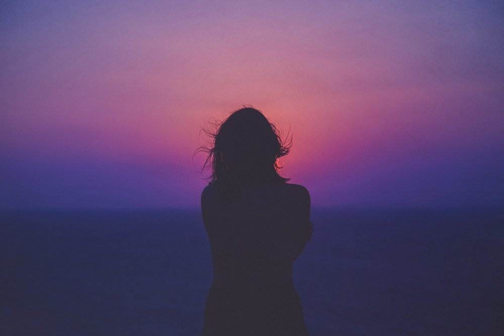 woman looking at pink sunrise