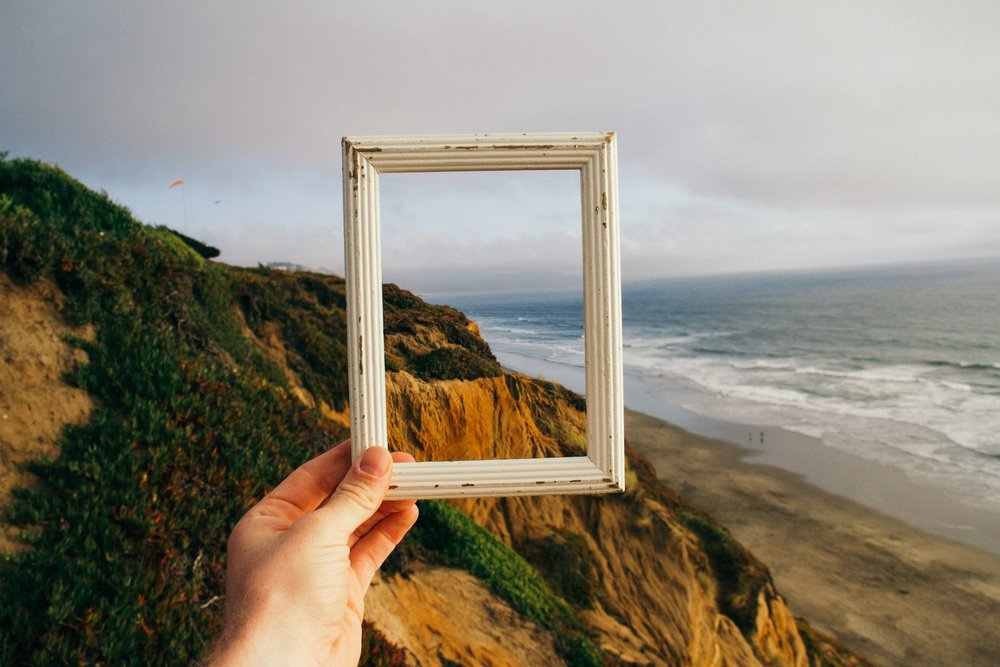 hand holding up picture frame to symbolize reframing