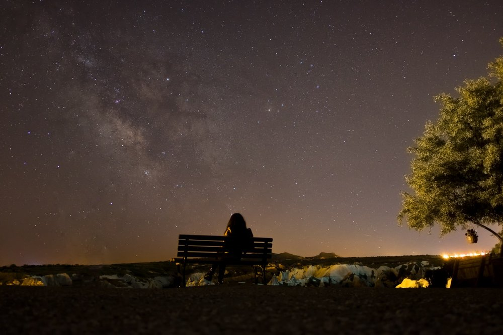lonely woman sitting on park bench beneath starry sky