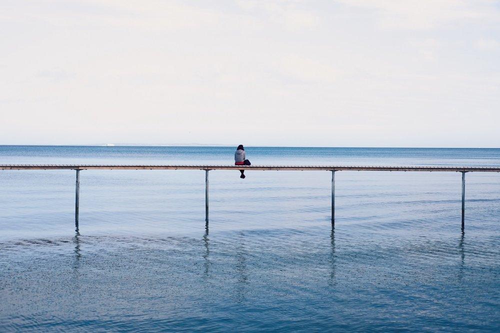 woman sitting on dock feeling alone