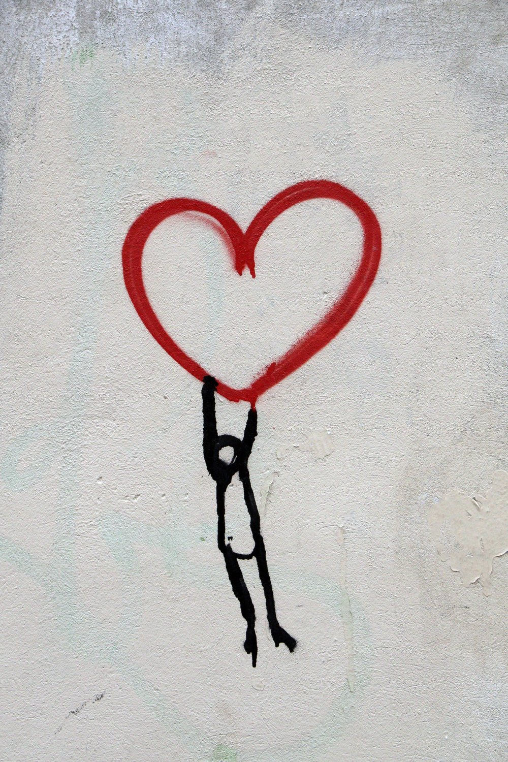 stick figure man hanging from a red heart