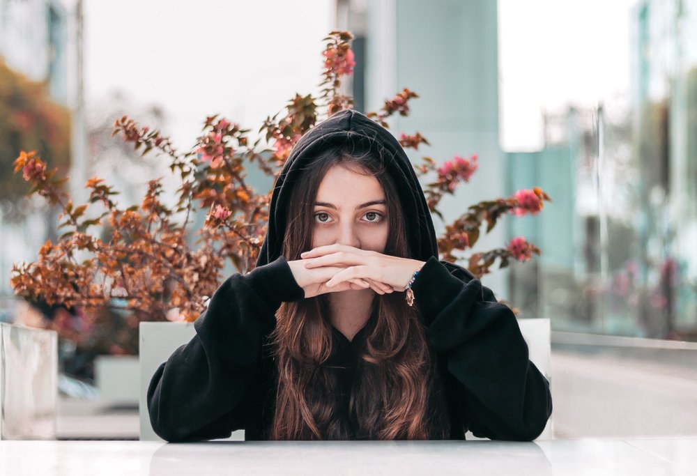 woman in hoodie staring straight ahead
