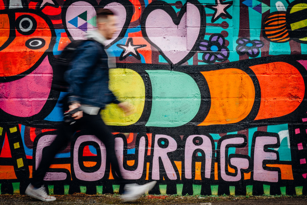 mentally healthy man walking past mural of the word courage