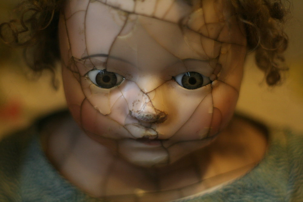 broken doll symbolizing broken woman