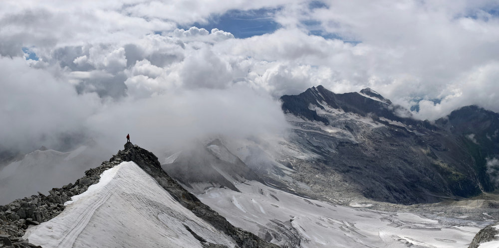 man standing on top of mountain looking for purpose