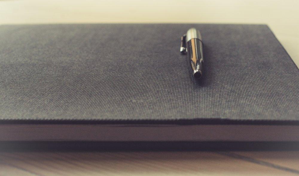 black pen on black notebook