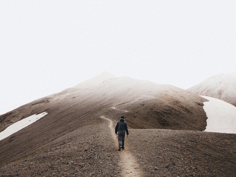 man walking alone on mountain trail