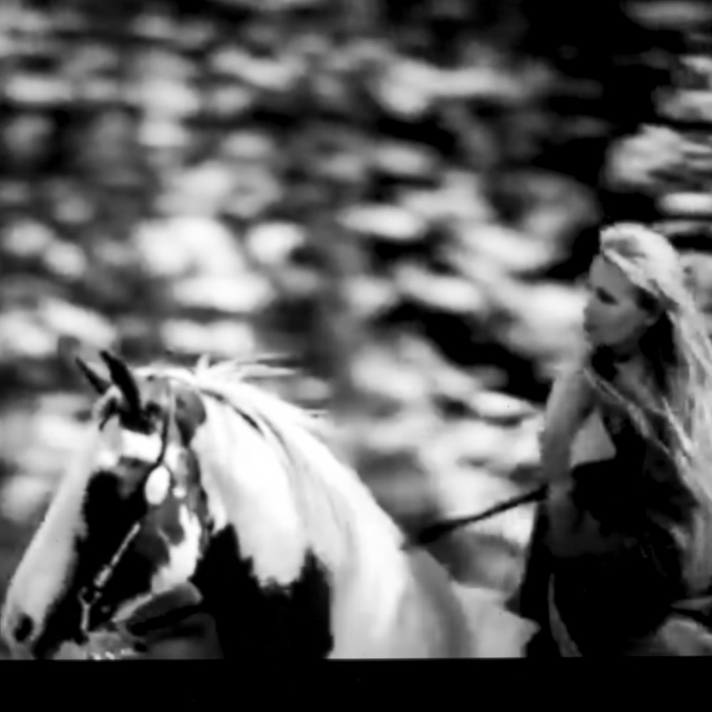 Robbie Williams, Feel.   Frame out of the music video, really shot in the western style. She is riding an amazing, awesome, great horse, and who can tell me where I can find an oversized coat as the one she is wearing, please phone me.