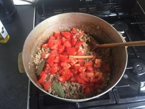 - Add tomatoes, the cinnamon stick and bay leaf. Leave on a medium heat to simmer while you make your sauce. Stir occasionally.