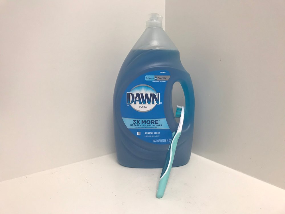Aubrey keeps a toothbrush and Dawn liquid soap by the washing machine to scrub stains.