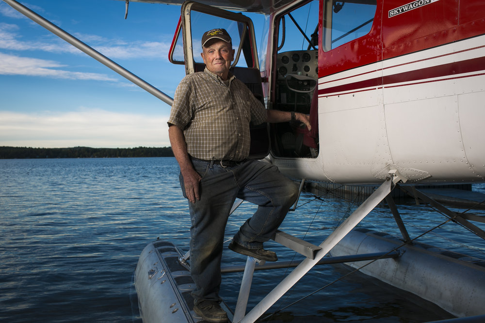 """George Dunn, 85, has had a lifelong passion for flying. He first got his license in 1952 and now shares that passion with seven other members of his family who fly and own planes, including his son who now flies KC-135s for the Air National Guard in Bangor. He and his family, known as """"The Flying Dunn's,"""" have been part of the Beech Hill Pond community for several years—Dunn has lived on the pond, year round, for more than 45 years and hosts an annual Fourth of July event at his hanger that draws more than 1,000 people each year."""