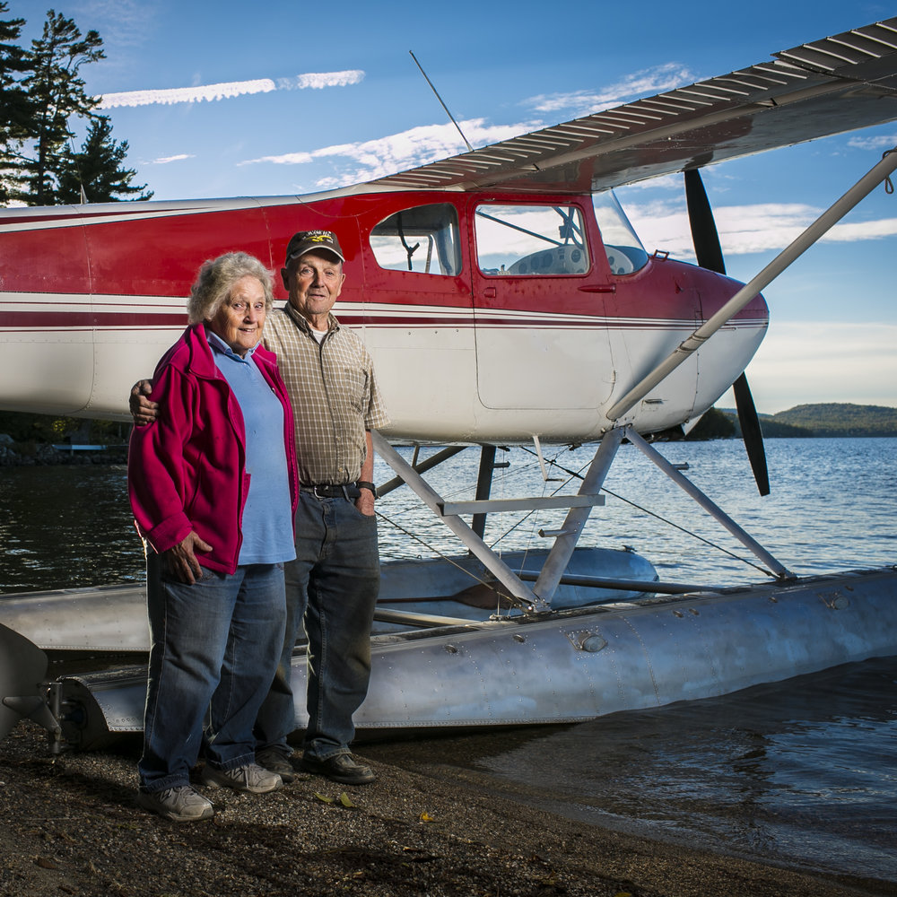"""George Dunn and his wife Donna have been together 63 years and living on the pond for more than 45 of those years. George Dunn, 85, has had a lifelong passion for flying. He first got his license in 1952 and now shares that passion with seven other members of his family who fly and own planes, including his son who now flies KC-135s for the AirNational Guard in Bangor. He and his family, known as """"The Flying Dunn's,"""" have been part of the Beech Hill Pond community for several years—Dunn has lived on the pond, year round, for more than 45 years and hosts an annual Fourth of July event at his hanger that draws more than 1,000 people each year."""