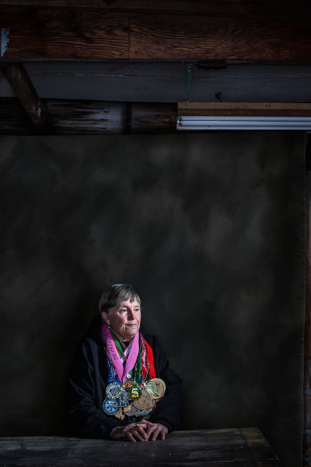 """Robin Emery, 72, of Lamoine, Maine has been running races for more than 50 years and logged enough miles to circumnavigate the globe one and a half times. Participating in approximately 30 races a year and running every day, she has pushed through physical adversity, such as once suffering a frozen eyeball due to weather conditions (she now runs with ski goggles in colder temps), and also broken through societal norms. When Robin signed up to run her first race in 1972, she was the first woman to ever enter the race. """"Women weren't supposed to sweat or be competitive then,"""" she said. """"It wasn't feminine."""" After entering the race and completing it three years in a row, she was finally given recognition: a basketball trophy, with a man on top. Photographed here in the garage of her family's home since the early 1900s, Robin's house is now filled with a life story of trophies, medals, race photos , plaques and memories from the myriad races she's won and participated in over the decades. Robin, who also was an elementary school teacher for more than 50 years, has a long-standing legacy in Maine. She was the second woman to ever be inducted into the Maine Running Hall of Fame, and also has a trophy named after her at that same Labor Day race."""